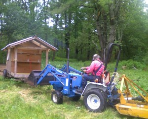 Jim pulls the mobile hen house to a new spot so the hens will have fresh greens and bugs to munch on.