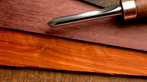 color photo: Jim's detailing gouge with Purpleheart, Padauk and Wenge in the background