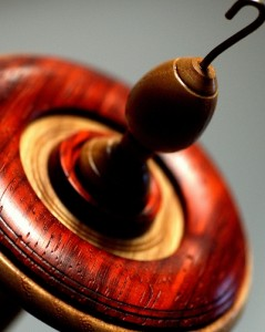 color photo: closeup of a handspindle's whorl -- woods: orange Padauk and creamy Ash